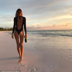 Baby got back! Elle Macpherson, 53, revealed her famous frame in a backless one-piece swimsuit as she hit the beach for a casual stroll on Tuesday