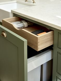 This hidden drawer above an integrated pull-out bin is great for storing bin liners, keeping your kitchen cupboards organised. Shaker cupboards painted in Farrow & Ball Green Smoke (No. Kitchen Pull Out Drawers, Built In Kitchen Cupboards, Kitchen Cupboard Organization, Hidden Kitchen, Kitchen Pulls, Grey Kitchen Cabinets, Cupboard Storage, Shaker Cabinets, Closet Organization