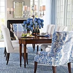 Love the rug and the blue and white patterned chair, hydrangeas and curtains.