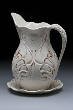 Lora Rust. Pitcher & Plate Set with Peacock Pattern; porcelain; clear glaze with rutile wash; fired to cone 6 oxidation; pitcher: 26.7cm h x 24.1cm w x 17.8cm d, plate: 2.5cm h x 20.3cm w x 20.3cm d . $300