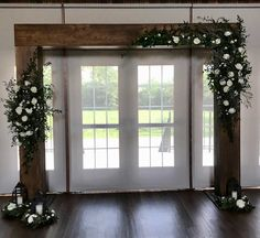 Wood arch with floral sprays in all white and mixed greenery, lanterns at the base.