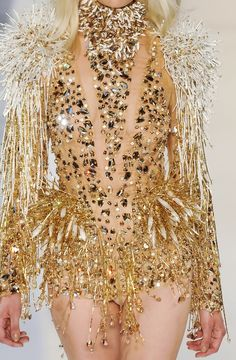 • Intricate gold detail • White firework shoulders • Low cut out • High neck • Beads, jewels • Glamorous