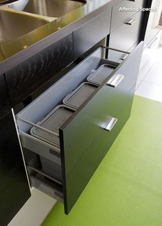 Undersink drawer. Now here's a better use of the limited and often awkward space below the sink: hiding the compost, recycling and garbage. The bins are accessed by opening the shallow sink drawer.