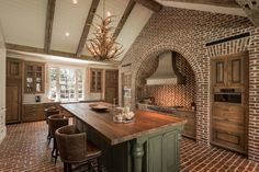 Rustic kitchen with exposed red brick walls and floors, reclaimed wood countertops, olive green island cabinets and brown leather barstools | Thompson Custom Homes