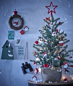 A medium-sized Christmas tree decorated with bird-themed ornaments and placed on a table against the wall. The grey wall behind is decorated with more bird themed items such as binoculars and bird boxes of various sizes.