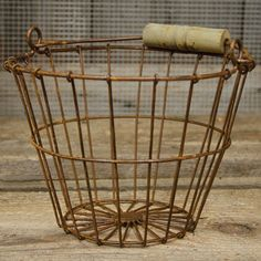 "The Wire Egg Basket is a perfect farmhouse display piece for kitchen goods, eggs, towels, or soaps. Rusted metal wire basket with tapered sides and a weathered wooden handle. 6"" H, 8"" in diameter at l"