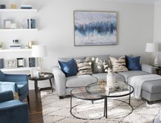 A welcoming interior living room should always make a statement! This interior decor worked around the beautiful abstract art by pulling out those blue & gold tones in the pillows, accent chairs, and shelving display. Nesting tables are a great use of space and perfect when entertaining to extend the table out when you need it. | Camden Lane Interiors - www.camdenlaneinteriors.com