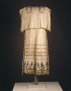 Probably Yanktonai Sioux, Native American. Strap Dress with Red and Green Embroidery, early 19th century. Emulsion cured buckskin, dyed porcupine quills, glass beads, tin and copper tinklers, thread, sinew and pigment, 46 x 21 in.  (116.8 x 53.3 cm).