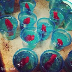 Fishbowl shots 1 cup uv blue raspberry  1/2 cup coconut rum 1/2 cup peach schnapps 6 packets gelatin Gummy bears Swedish fish Small plastic/paper cups