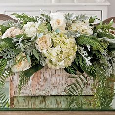Earthy Centerpiece -- A hollowed-out log is filled with roses, hydrangeas, and Leyland cyprus for a luxurious yet earthy look.