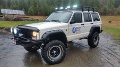 1996 XJ Cherokee SE: Borla Header High Flow Cat Bored throttle body and spacer 5in coil lift in front, 5in leaf +3deg in back Tom Woods rear drive shaft SYE kit on NP231 Xfer case Eaton Tru-Trac locker in rear Dana 35 Smitty-Bilt XRC winch and bumper Smitty-Bilt roof rack Cree LED on rack, HID on front Alpine audio system