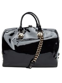 Patent leather handbag in black from Versace. This patent leather bowler bag featers double top handles, optional long chain shoulder strap, decorative side buckles, and top two-way zipper and buckle closure. Has cotton lining, with two slot and one zipper pocket. Measures 9.5