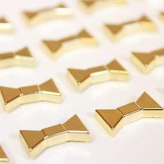 Kate Spade New York Gold Bow Push Pins. http://www.urbangirl.com/Products/kate-spade-new-york-Push-Pins__KSP134130.aspx