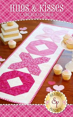 """Hugs & Kisses Table Runner Kit Dress up your table for a Valentine's Day party with this cute Hugs & Kisses Table Runner! This runner features gorgeous pink fabrics that come together to make a neat ombre effect. This table runner is perfect for a beginner quilter as it is super simple to put together. Finished size is 14½"""" x 44½""""."""