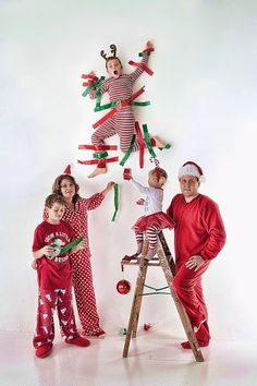 15 Hilarious Holiday Family Photo Ideas You Should Steal via Brit + Co.  - 15.Taped to the Wall: The naughtiest kid on Santa's list deserves to get taped to the wall, no? Regardless, it will definitely make for a WTF moment worthy of phone calls from Grandma and Grandpa. (viaHighlite Photography)
