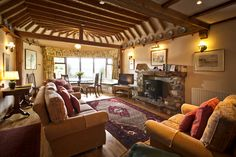 Large open plan lounge with vaulted oak beamed ceiling, feature stone fireplace, and solid oak flooring.