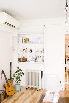 壁面にスリムな棚を作成。見せる収納としておしゃれな雑貨を飾りたくなりますね。暖房器具がすっぽり収まるサイズで機能性も◎です。