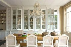 Dining room in Belgium with white drawers and cabinets with glass fronts, cane back chairs, a chandelier, farmhouse style wood table