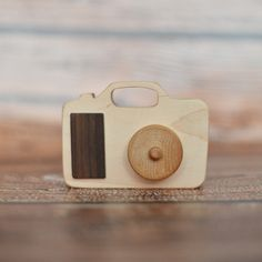 """Wooden Camera Teether. This is the perfect teether for your """"little photographer"""". With cured wood this wooden teether is perfectly chewable and safe for your little one. The lens is detached giving you the ability to spin it. Great for photographer's kids or as a baby shower gift! Pin this to your wishlist photographers!!"""