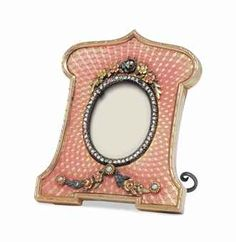 A JEWELLED FOUR-COLOUR GOLD-MOUNTED GUILLOCHÉ ENAMEL PHOTOGRAPH FRAME MARKED FABERGÉ, WITH THE WORKMASTER'S MARK OF VIKTOR AARNE, ST PETERSBURG, 1899-1904 Rectangular with an arched crest, on bracket feet, enamelled overall in translucent salmon pink over a sunburst diaper pattern guilloché ground, applied with varicolour gold flower sprays and seed pearl-set garlands above and below the oval diamond-set bezel, within rose gold border.
