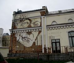 Face carved into a wall by Alexandre Farto aka Vhils