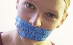 A woman with a tape measure wrapped around her mouth