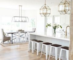 In this example of light-coloured kitchen, where white is predominant in each accessory, lighting fixtures with a metal structure outline the interiors together with the dark cushions of stools. Beach Interior Design, Bathroom Interior Design, Kitchen Interior, Interior Decorating, Interior Designing, Pallet Home Decor, Diy Home Decor Projects, Unique Home Decor, Cheap Home Decor