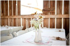 To save money on centerpieces we used old floral hankies and white milk vases found at local thrift stores.  The baby's breath for all of the tables was super cheap and the other flowers were found in the ditch on the day of the wedding.