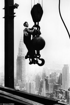 A construction worker hangs from an industrial crane during the construction of the Empire State Building