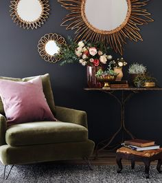A deep-grey wall colour — Peppery (MQ2-62) by Behr — gives this space a cosy feel, while a mossy-green velvet chair and blush-pink pillow inject warmth. A mix of planters, brass accents, and a vintage table and footstool layer patina into the room.