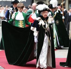So cumbersome was the Queen's long mantle, a page boy, dressed in bright green, was enlisted to help hold it up at times