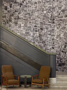 A black and white mural of thousands of graffiti stickers graces the wall behind the staircase in the lobby of the Roman and Williams-designed Ace Hotel New York. #hospitalitydesignmagazine #hospitalitydesign #hdmag #places #design #designer #hotels #interview #bradwilson #acehotel