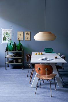 Een collectie designstoelen van onder andere Wim Rietveld en Eames geeft de tafel karakter, net als de opvallende houten lamp erboven.