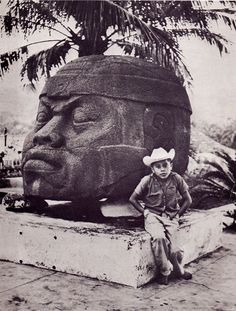 Mexican boy posing in front of an Olmec head.
