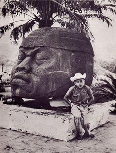 Mexican boy posing in front of an Olmec head.