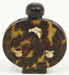 Antique hand carved tortoise shell and ivory snuff bottle. Translucent mottling to shell. Has relief carved designs throughout depicting flowers and fruit. Has ivory overlay fruit and flowers.