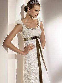 Vestidos de novia Cuello en U, a los hombros ligera manga. Corte imperio con lazo bajo el busto, en contraste . Encaje de forma geométrica sobre un fondo liso.