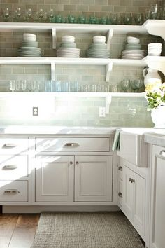 Chic Kitchen with beautiful tile for backsplash & the entire wall. Open Shelving displays beautiful dishware & glassware with light blue/gree  tile showing through.designed by alice lane
