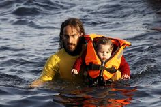 A volunteer lifeguard carries a baby as a half-sunken catamaran carrying around 150 refugees, most of them Syrians, arrives after crossing part of the Aegean sea from Turkey on the Greek island of Lesbos, October 30, 2015. REUTERS/Giorgos Moutafis