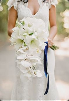 Modern white cascading bridal bouquet of white amaryllis and phalaenopsis orchids by  jade lee events #weddings #cascading #bouquet