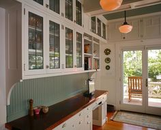 Contemporary cabinetry in '20s style. Beadboard. Cabinets with glass windows. Love.