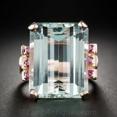 Dive into this cool and refreshing, swimming pool blue aquamarine, weighing in at 21 carats. The pretty pastel gemstone glistens between trios of round red rubies, all set in a Retro cocktail ring rendered 14K rose gold. Circa 1940s. The top measures 7/8 by 5/8 inch. Currently ring size 7 1/4.