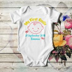 Personalized baby boy bodysuit, in black or white color with multicolor artwork, lap shoulders, short sleeves, and bottom snaps. Add the baby's name or whatever you like. Made of cotton in 4 sizes.