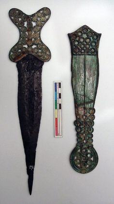 Iron and Copper Alloy Dagger and Sheath  Iron Age, Hallstatt D  Found Berkshire, England  c.600-550 BC    Iron dagger with ornate cast copper alloy cross-shaped hilt and matching decorated sheath. The decorative disks presumably held insets, possibly of coral.  Blade length: 27.8cm    Source: British Museum