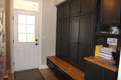 Black lockers in mud room with wood bench - extra storage in mud room cabinets - built-ins by Farinelli Construction