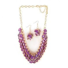 This jewelry set with orchid-hue gems, dramatically bunched and layered, create a striking accent to finish your favorite outfit. Faceted orchid-hue gems, dramatically bunched and layered, create a striking accent to finish your favorite outfit. The golden chain necklace features three rows of round purple stones, and the matching dangle earrings are the perfect accompaniment.
