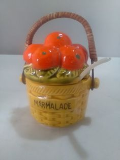 A lovely small individual marmalade pot with s basket handle and a small plastic spoon. It has a basket pattern round the base and oranges and leaves on the lid. It measures 5 inches to the top of the handle and is in perfect condition.