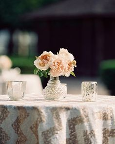For a formal affair in Rutherford, California, sequined chevron fabric and silver vessels holding a few peonies topped the cocktail tables, adding some glitz to the natural setting.