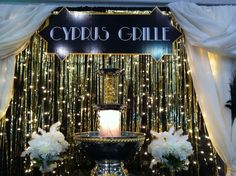 Great Gatsby themed booth I created for a work event. Repurposed sheers, white Christmas lights on black drape, gold foil door curtains, spray painted champagne bottles, punch fountain.