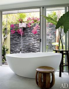 A Waterworks tub in the master bath faces a slate-walled waterfall shower created by Jungles; the tub and shower fittings are by Dornbracht, and the Indonesian low stool is from Archeo Gallery.